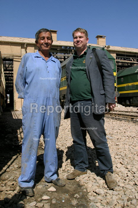 RMT member Alex Gordon stands in solidarity with a rail worker at the Baghdad maintenance depot. On the first solidarity trip, UK trade union members meet with representatives from the Workers Democratic Trade Union Movement WDTUM. Baghdad, Iraq. - Jess Hurd - 2003-10-06