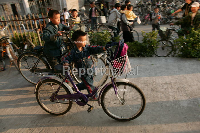 Chinese children return home on their bikes at the end of the school day. Jiaojiang, Taizhou, Zhejiang Province, China. - Jess Hurd - 2003-10-15