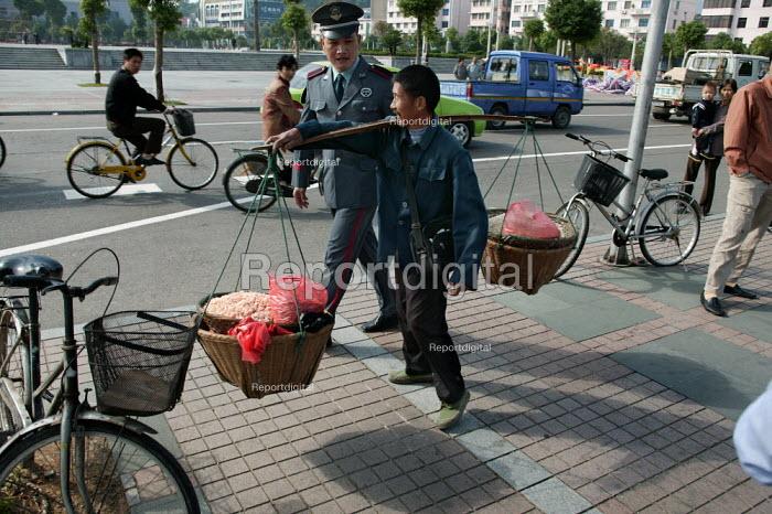 Chinese policeman moves on street rice seller. Linhai, Zhejiang Province, China. - Jess Hurd - 2003-10-16