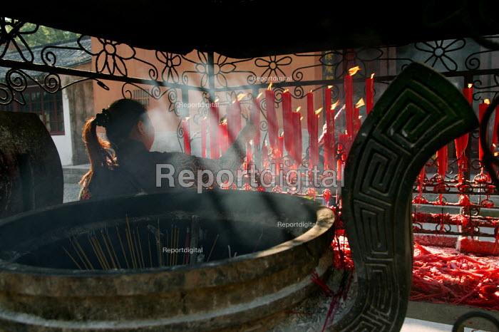 Woman lights candles at the Guoqing Buddhist Temple, Tiantai, Zhejiang Province, China. - Jess Hurd - 2003-10-17