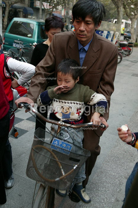 Father collects his child from school on his bike. Shanghai, China. - Jess Hurd - 2003-10-20