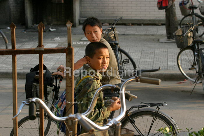Chinese children leave school by bike. Jiaojiang, Taizhou, Zhejiang Province, China. - Jess Hurd - 2003-10-15
