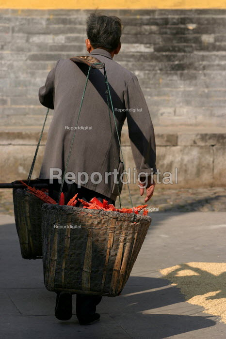 Monk carries away old candle wax at the Guoqing Buddhist Temple, Tiantai, Zhejiang Province, China. - Jess Hurd - 2003-10-17
