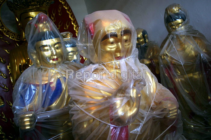 Wrapped carved Buddha for sale. Tiantai Buddhist City, Tiantai, Zhejiang Province, China. - Jess Hurd - 2003-10-17