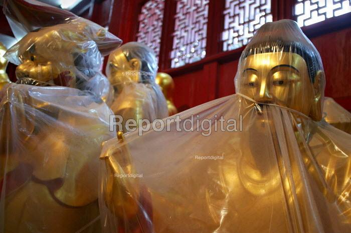 Wrapped carved Buddha for sale. Tiantai Buddhist City, Tiantai, Zhejiang Province, China. - Jess Hurd - 2003-10-17