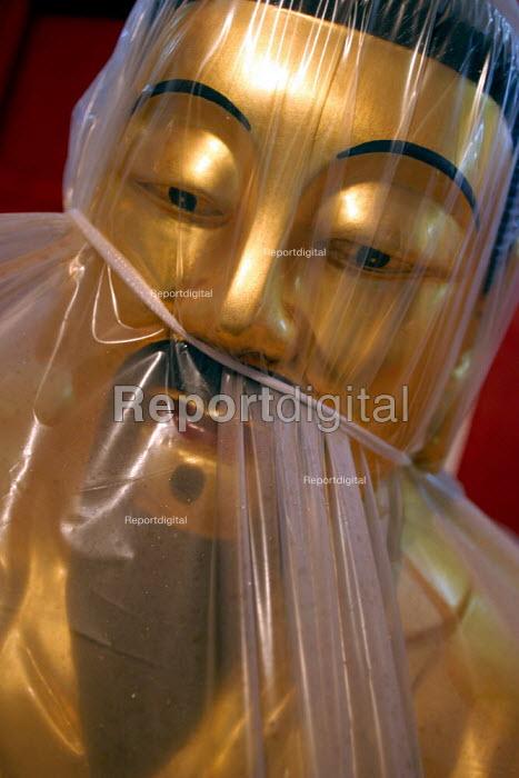 Wrapped carved wooden Buddha for sale. Tiantai Buddhist City, Tiantai, Zhejiang Province, China. - Jess Hurd - 2003-10-17