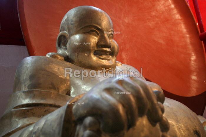 Carved wooden Laughing Buddha for sale. Tiantai Buddhist City, Tiantai, Zhejiang Province, China. - Jess Hurd - 2003-10-17