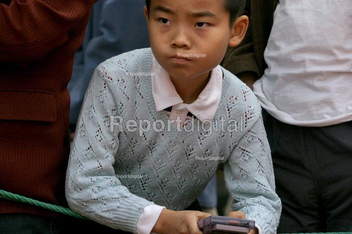Young boy plays an electronic game. Hangzhou, Zhejiang Province, China. - Jess Hurd - 2003-10-18