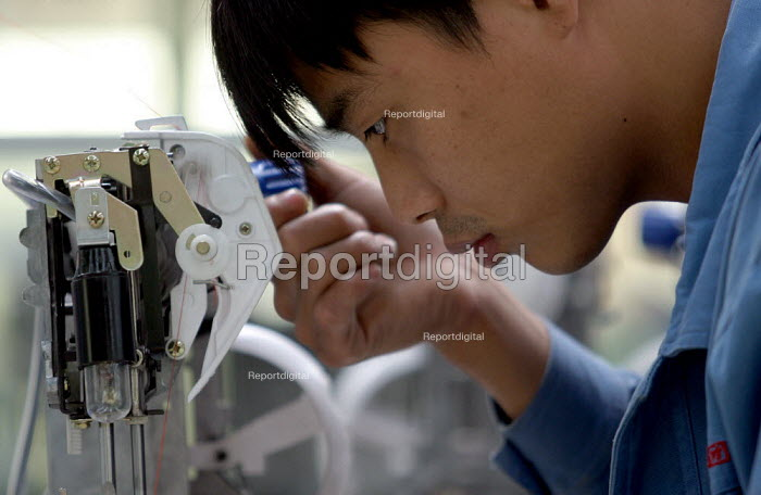 Chinese worker at the Feiyue Group Sewing machine factory. It is a privately owned industry on the outskirts of Jaojiang in the Taizhou Economic Development Zone, Zhejiang Province, China. - Jess Hurd - 2003-10-15