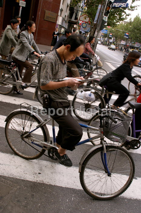 Man reads the morning newspaper as he cycles to work on a bicycle. Shanghai, China. - Jess Hurd - 2003-10-20