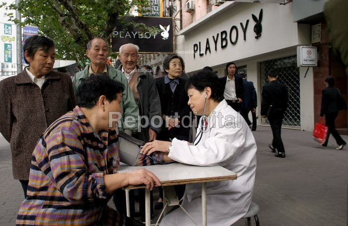 Pensioners get a free check up with blood pressure test on the pavement as part of a health and wellbeing project providing services once a month on the streets of Shanghai, China. Outside The Playboy Club. - Jess Hurd - 2003-10-20