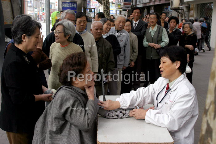 Pensioners get a free check up with blood pressure test on the pavement as part of a health and wellbeing project providing services once a month on the streets of Shanghai, China. - Jess Hurd - 2003-10-20