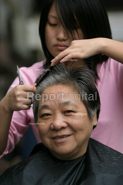Pensioners get a free haircut on the pavement as part of a health and wellbeing project providing services once a month on the streets of Shanghai, China. - Jess Hurd - 2003-10-20