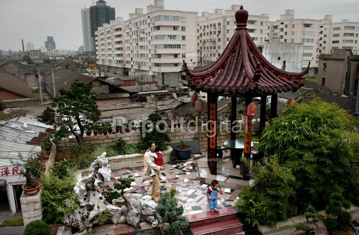 Chinese grandparent looks after her grandchildren in a traditional bonsai tree garden, overlooking an area soon to be developed. Wenzhou Nanya model Housing Community, Zhejiang Province, China. - Jess Hurd - 2003-10-26