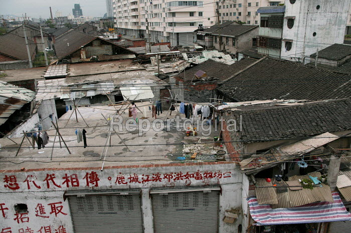 Chinese family on the rooftop of their shanty home which is soon to be developed. Wenzhou, Zhejiang Province, China. - Jess Hurd - 2003-10-26