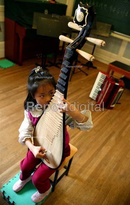 Child is taught in a music lesson. Children's Palace China Institute Welfare. A private school dedicated to the Arts and Science. Shanghai, China. - Jess Hurd - 2003-10-20