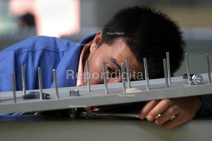 Chinese worker at the Feiyue Group Sewing machine factory. It is a privately owned industry on the outskirts of Jaojiang in the Taizhou Economic Development Zone, Zhejiang Province, China. - Jess Hurd - 2003-10-26