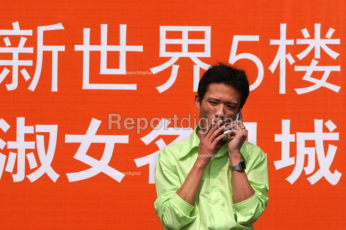 Chinese man smoking a cigarette whilst on a mobile phone, Shanghai, China - Jess Hurd - 2003-10-26