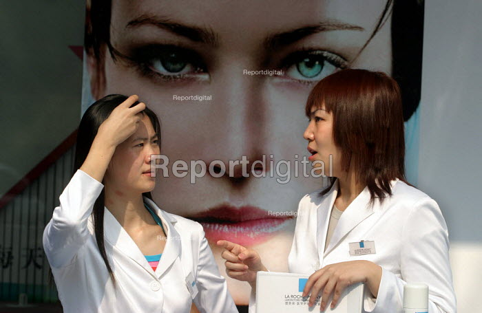 Cosmetics sales woman sits in front of westernised beauty advertising for La Roche-Posay. Nanjing Road, Shanghai, China. - Jess Hurd - 2003-10-26