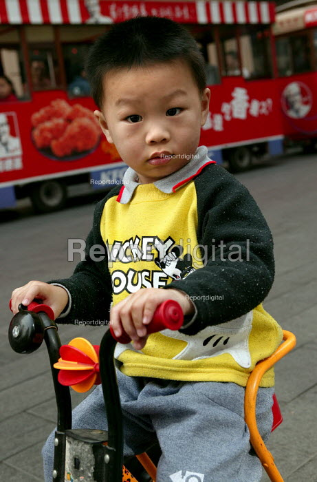 Young Chinese boy with a Mickey Mouse sweater and a trike. Nanjing Road, Shanghai, China. - Jess Hurd - 2003-10-20