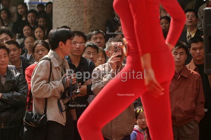 Chinese woman models thermals, being photographed. Nanjing Road, Shanghai, China. - Jess Hurd - 2003-10-20