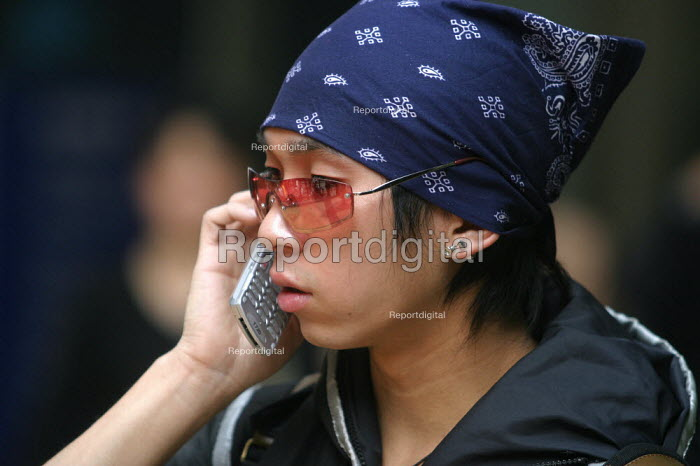 Chinese fashion conscious youth on a mobile phone. Nanjing Road, Shanghai, China. - Jess Hurd - 2003-10-26