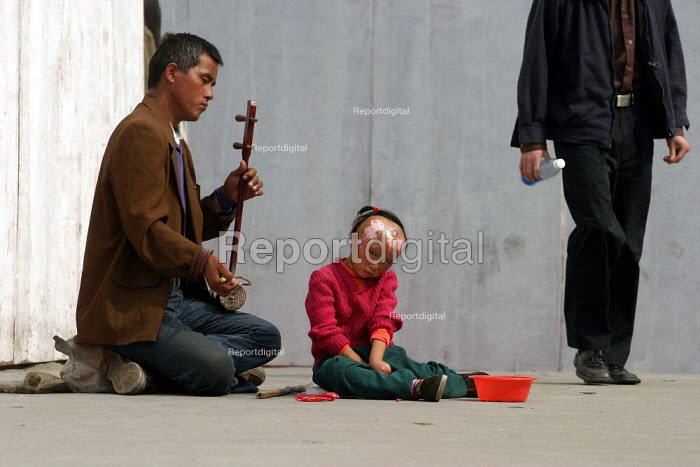 Father begs with his severely disfigured daughter, Shanghai, China. - Jess Hurd - 2003-10-21