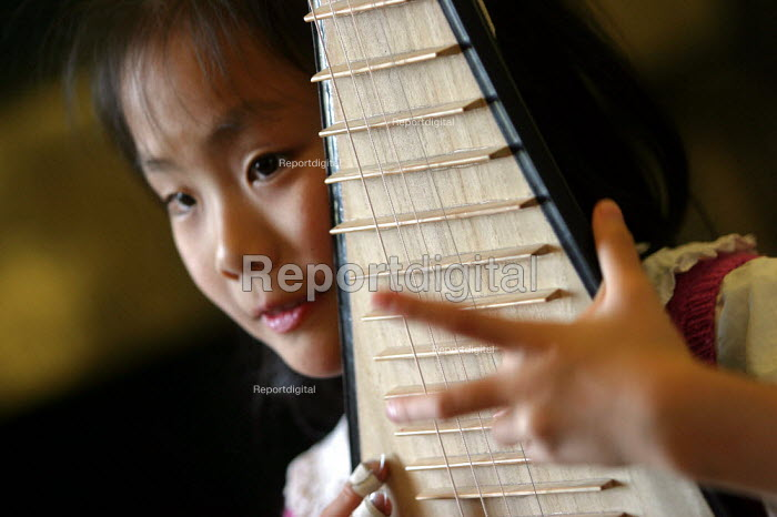Child is taught in a music lesson. Children's Palace China Institute Welfare. A private school dedicated to teaching the Arts and Science. Shanghai, China. - Jess Hurd - 2003-10-20