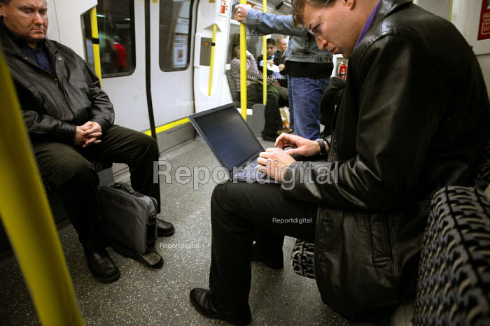 Man uses laptop computer on a London Underground tube train. - Jess Hurd - 2003-11-03
