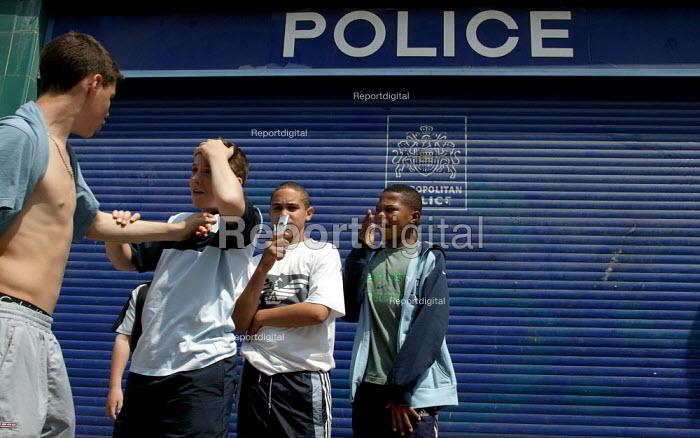 Youth outside closed local police station, Chrisp Street Market, Poplar, East London. - Jess Hurd - 2003-06-14