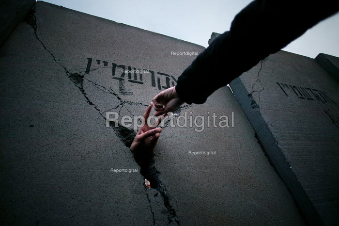 Pro Palestinian activist thrusts his hand through a replica Separation wall representing the concrete wall erected by Israeli forces through the West Bank. European Social Forum demonstration, Paris - Jess Hurd - 2003-11-15