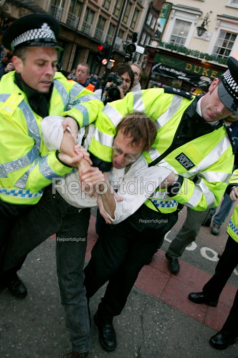 Police manhandle a protester and making an arrest. High level police security operation as anti war protesters gather in London to protest against the State visit of US President George Bush to the UK - Jess Hurd - 2003-11-19