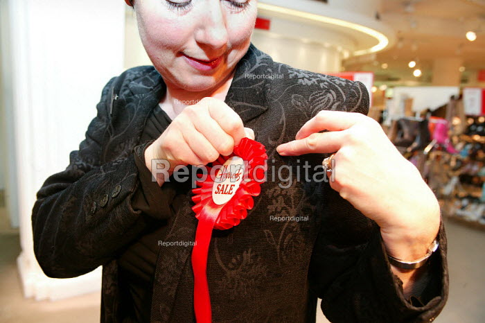 Harrods sales asssistant pins a rosette to her jacket in preparation for the opening day of the Harrods Sale. London. - Jess Hurd - 2003-12-30