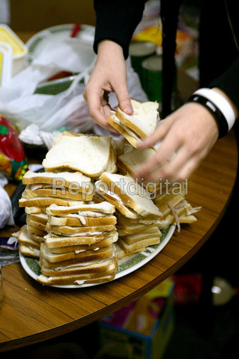 Volunteer makes turkey sandwiches for the homeless. Christmas Day night at the Newham Night shelter for the homeless, 170 Harold Road, East london. - Jess Hurd - 2003-12-25