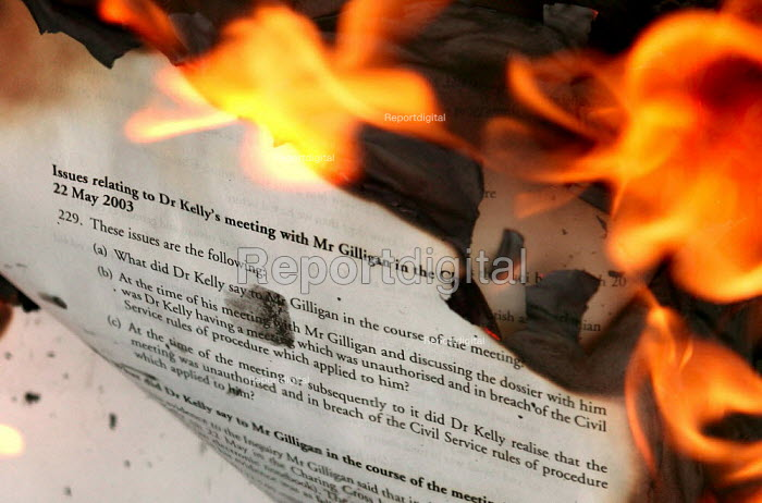 A page of the Hutton Report concerning Dr Kelly's meeting with BBC journalist Andrew Gilligan is consumed by flames as Anti War campaigners burn a copy of the Hutton Report, and claim the inquiry into the death of Dr David Kelly was a whitewash. Downing Street, Westminster. - Jess Hurd - 2004-01-31