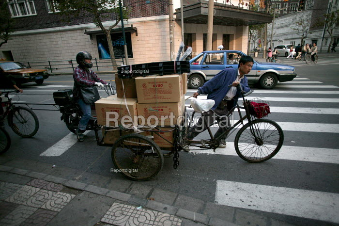 Man cycles to work on a bicycle. Shanghai, China. - Jess Hurd - 2003-10-20