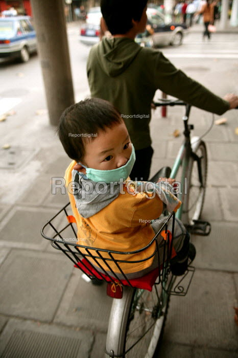 Woman with her child on a bicycle with a face mask. Shanghai, China. - Jess Hurd - 2003-10-20