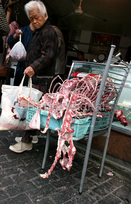 Chinese woman shops at a street butcher with an animal carcass left outside. Shanghai, China. - Jess Hurd - 2003-10-20