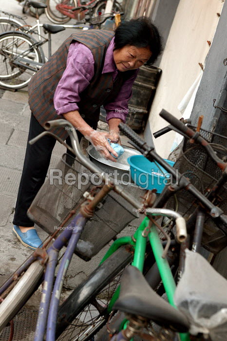 Chinese woman washes her pots on the pavement. Shanghai, China. - Jess Hurd - 2003-10-20