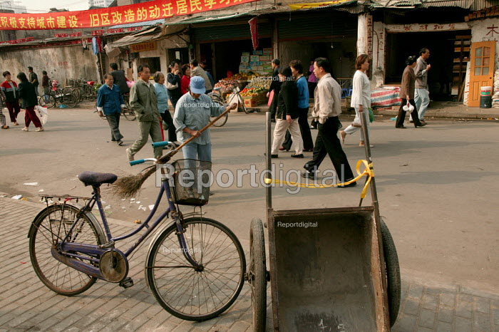 Workman sweeps the street in the Old Town. Shanghai, China. - Jess Hurd - 2003-10-20