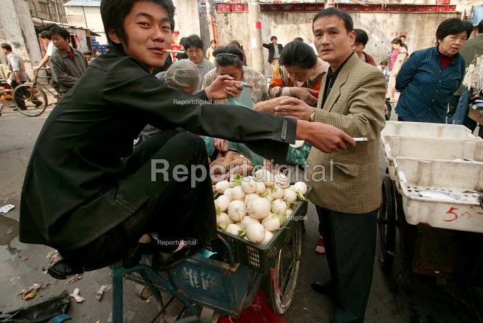 Young Chinese street vendor sells turnips and sweet potato in the Old Town Ghost Market, Shanghai, China. - Jess Hurd - 2003-10-26