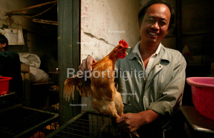 Chinese chicken vendor in the Old Town Ghost Market, Shanghai, China. - Jess Hurd - 2003-10-26