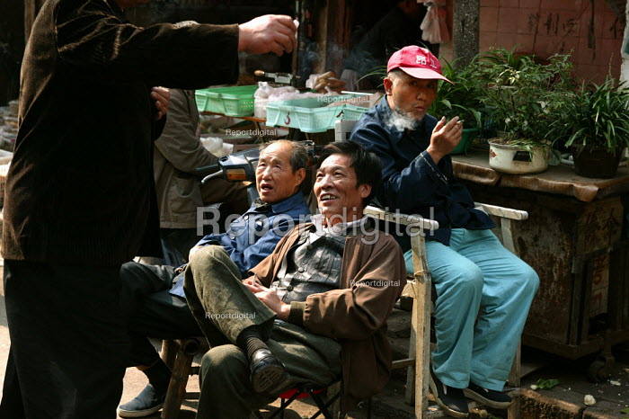 Old Chinese men smoke cigarettes. Old Town Ghost Market, Shanghai, China. - Jess Hurd - 2003-10-26
