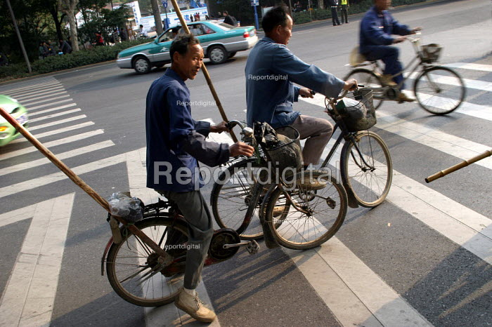 Chinese men travel to work on bicycles. Hangzhou, Zhejiang Province, China. - Jess Hurd - 2003-10-18