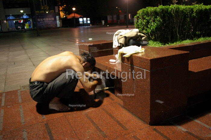 Chinese man, possibly a migrant worker, washes himself in a water hydrant early morning, Nanjing Road, Shanghai, China. - Jess Hurd - 2003-10-20