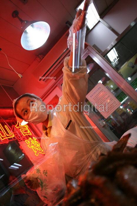 Woman in a fast food take away restaurant. Shanghai, China. - Jess Hurd - 2003-10-20