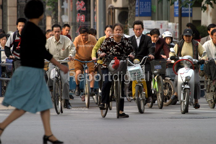 Commuters cycles to work on a bicycles. Shanghai, China. - Jess Hurd - 2003-10-20