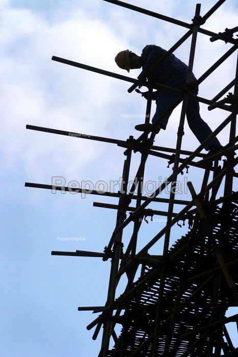Chinese building worker on a construction site bolts together scaffolding. Shanghai, China. - Jess Hurd - 2003-10-20