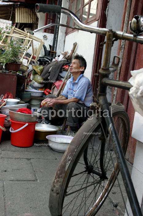 Old Chinese man washes his clothes in the street. Old Town, Shanghai, China. - Jess Hurd - 2003-10-26