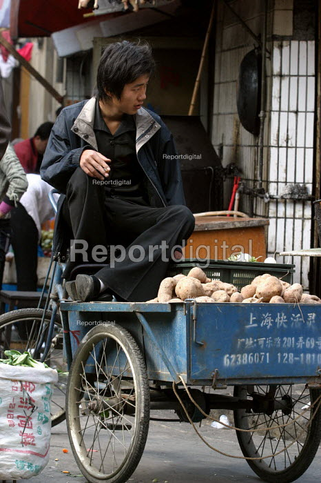 Young Chinese street vendor smoking a cigarette sells turnips in the Old Town Ghost Market, Shanghai, China. - Jess Hurd - 2003-10-26